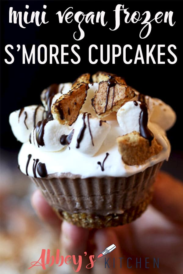 pinterest image of Hand holding s'mores cupcakes with text overlay