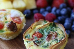 close up image of keto egg cups with fresh berries in the background on a wooden surface