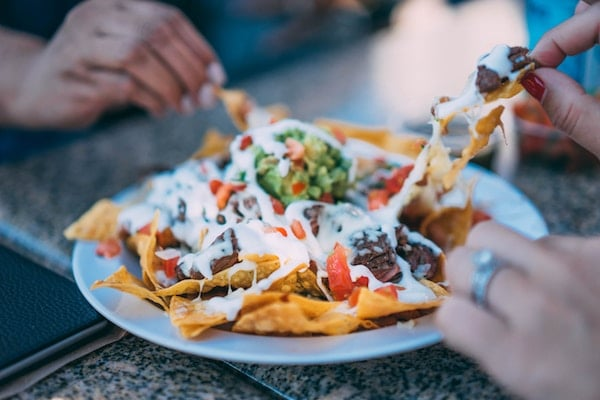 various hands taking chips out of a plate of nachos