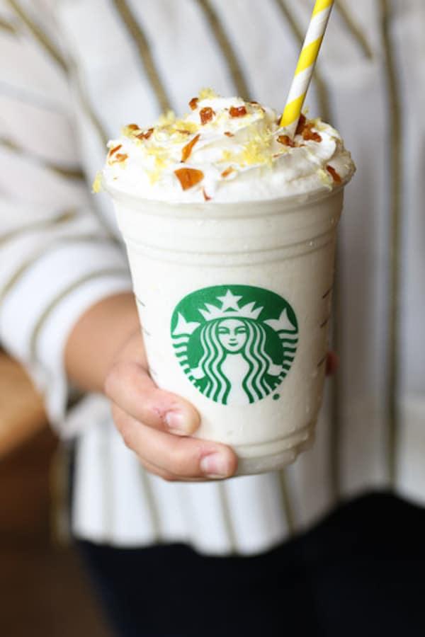 Hand holding lemon bar frappuccino.