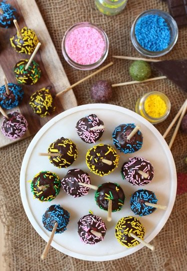 Chocolate cake pops covered in sprinkles served on a white plate.