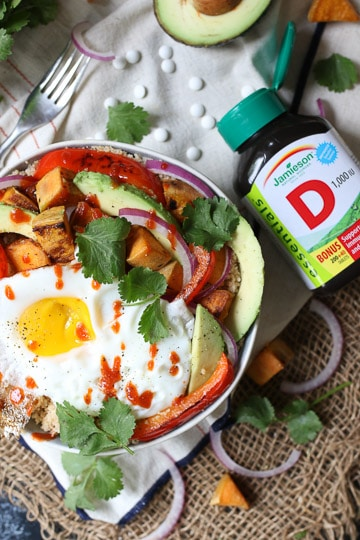 birds eye view of a buddha bowl garnished with cilantro and hot sauce next to a bottle of vitamin D supplements
