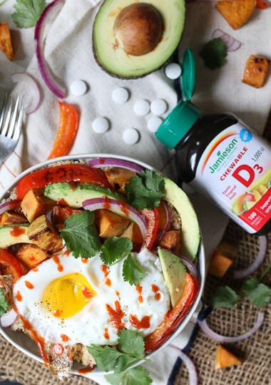 birds eye view of a nourish bowl topped with an egg next to a bottle of vitamin D supplements