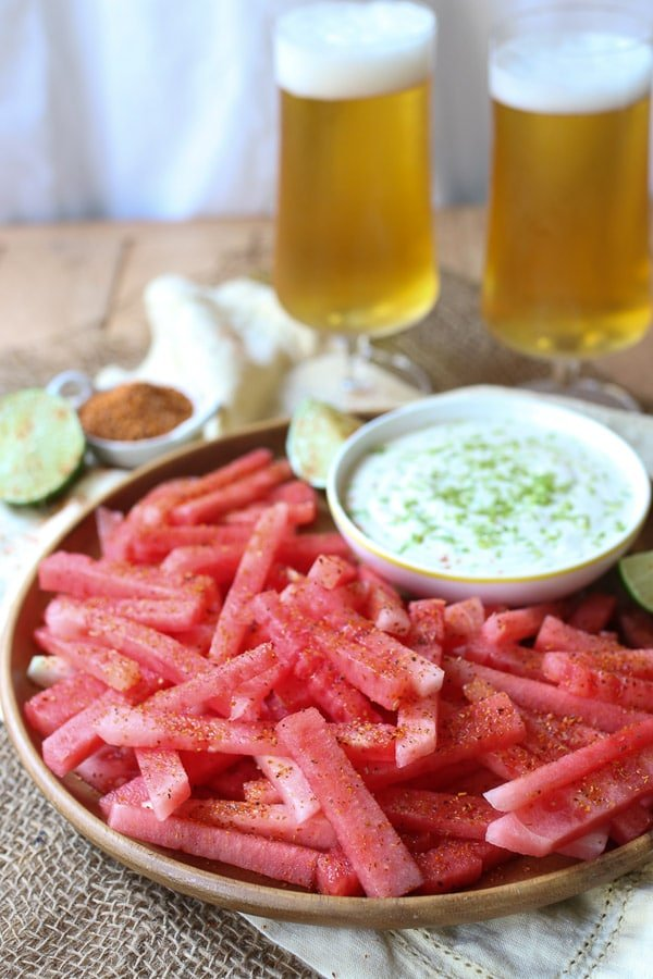 Watermelon fries served on a wooden plate next to a dip.
