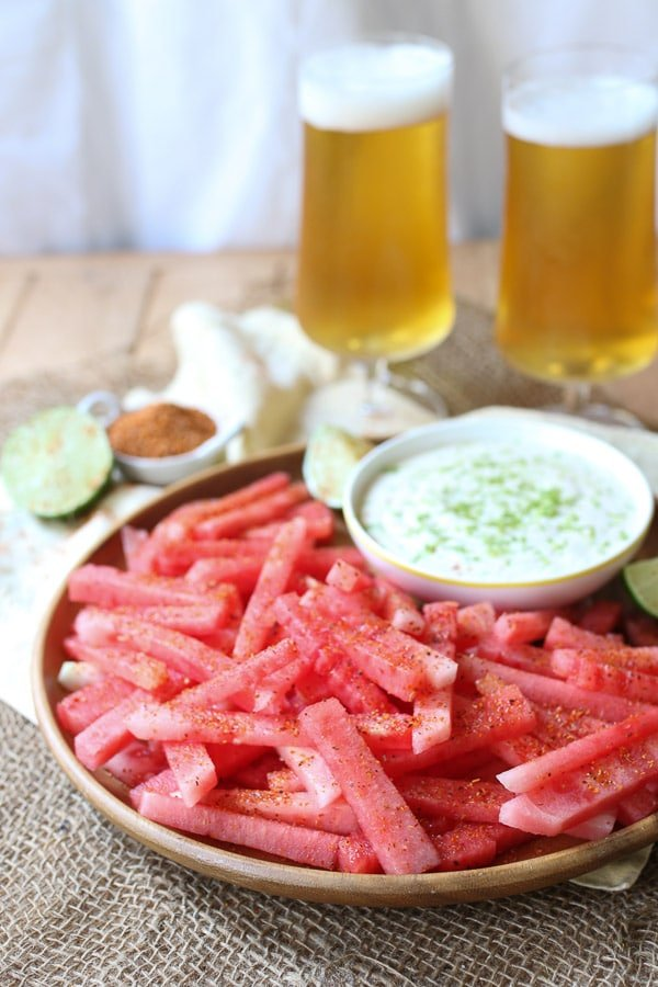 Watermelon fries on a wooden plate next to dip.