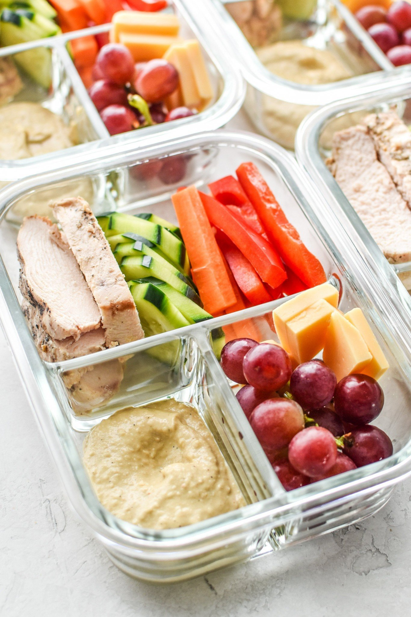 Chicken and veggies with hummus in lunch boxes.
