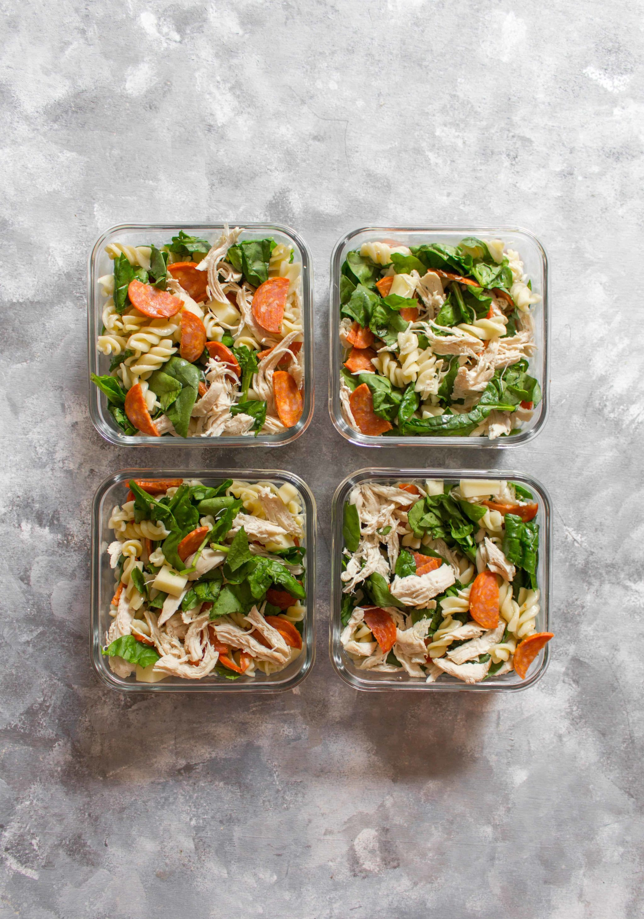 Pasta and veggies in four lunch boxes.