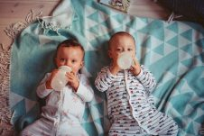 Two babies drinking from bottles while lying on a teal blanket.