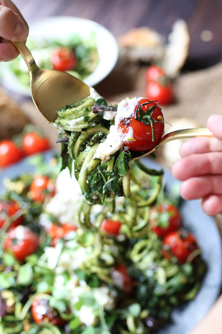 fork taking a bite out of keto beet green pesto zoodles garnished with tomatoes and cheese