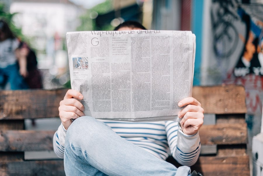 person reading a newspaper on a bench