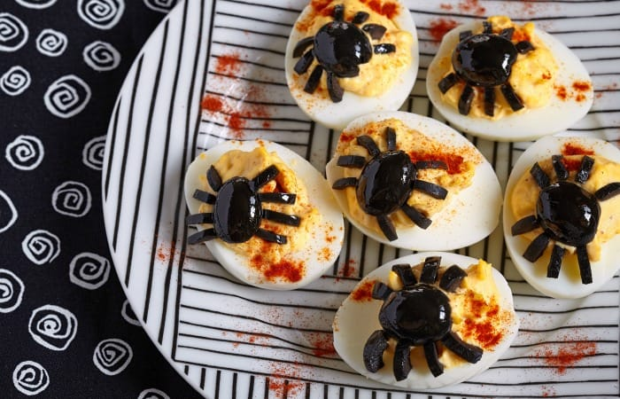 Devilled eggs with spider decorations on a plate.