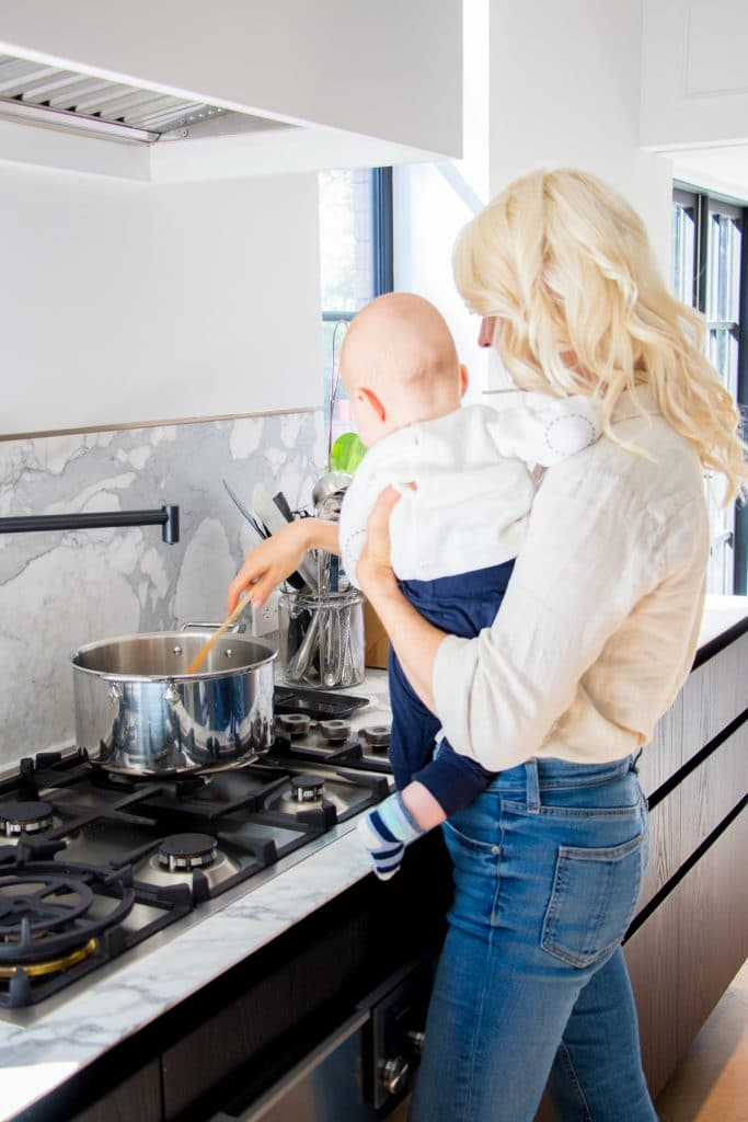 Woman holding her baby next to a stove in their kitchen.
