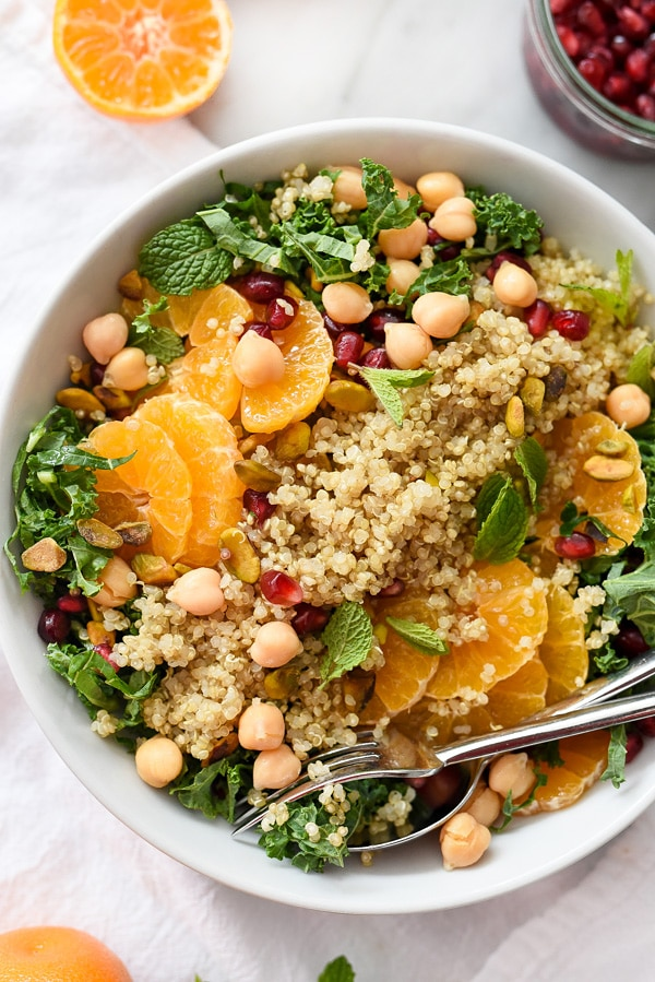 close up of gluten free quinoa and kale protein salad in a white bowl garnished with nuts and herbs