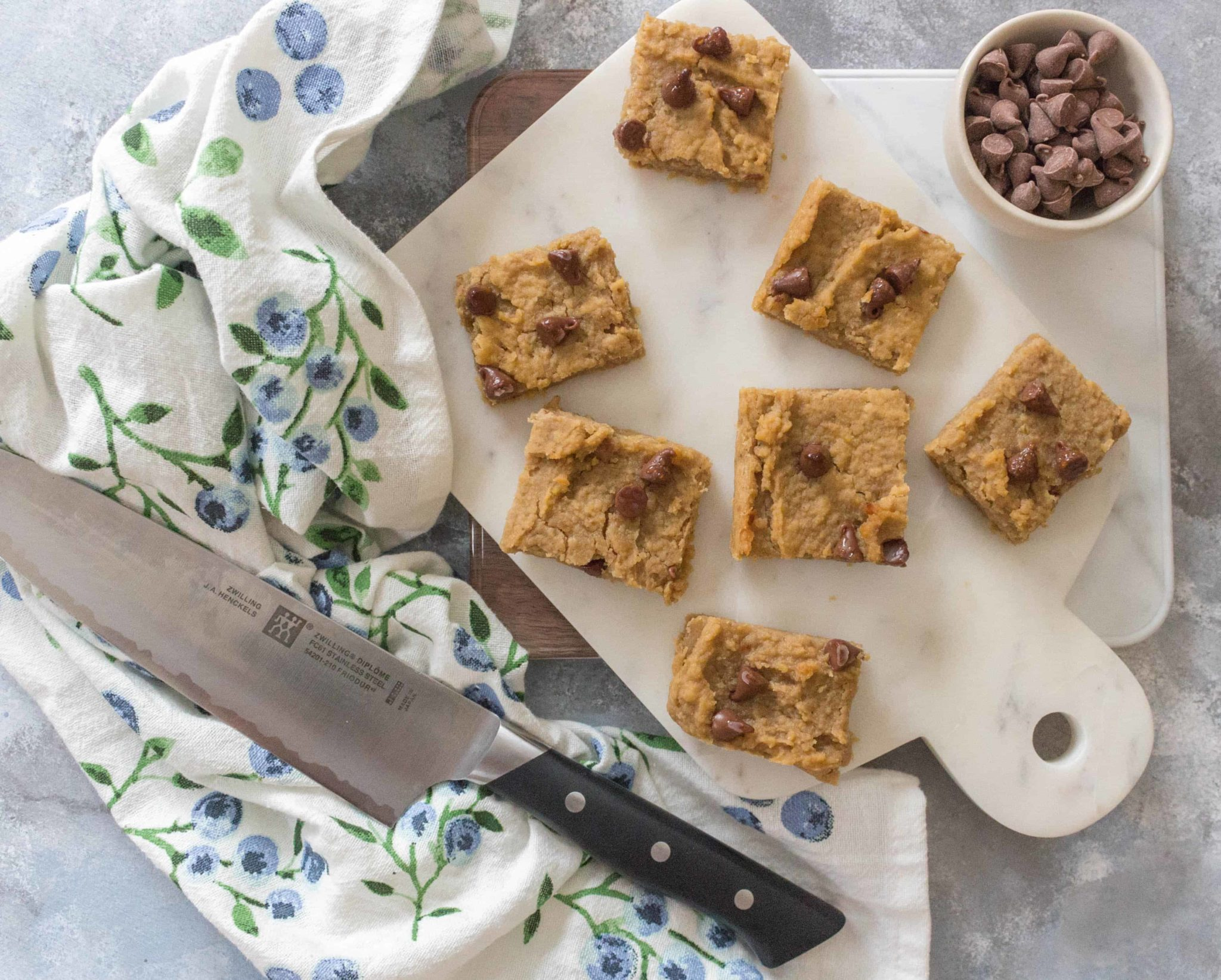 birds eye view of gluten free chickpea peanut butter blondies on a white serving board