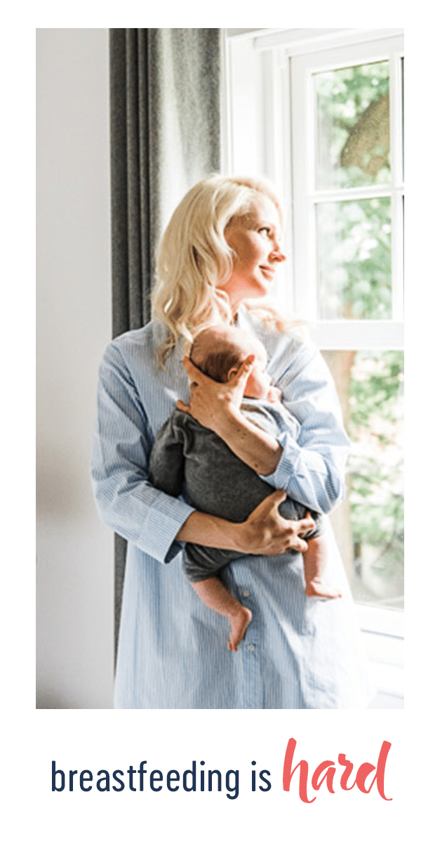 abbey holding baby E next to a window
