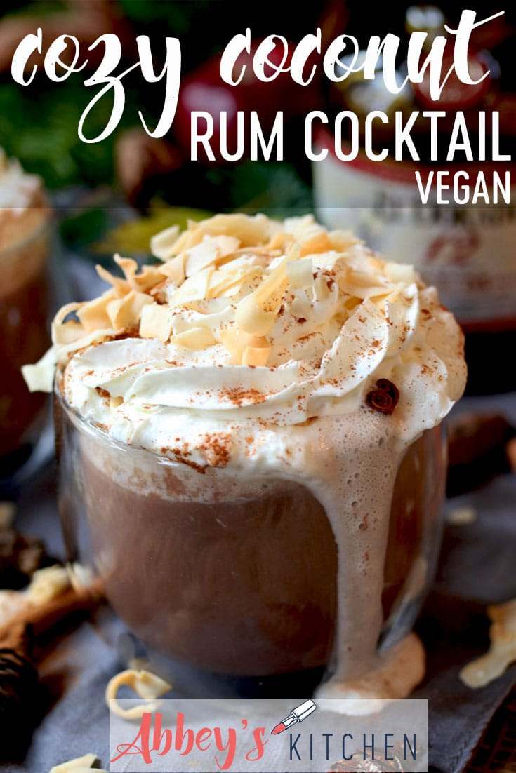 pinterest image of warm coconut rum cocktail in a clear glass garnished with whipped cream with text overlay