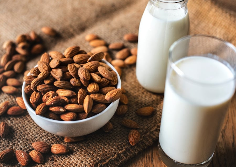 two jars filled with almond milk next to a bowl of almonds