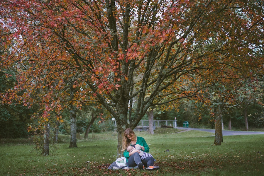 woman holding her baby under a tree in a park