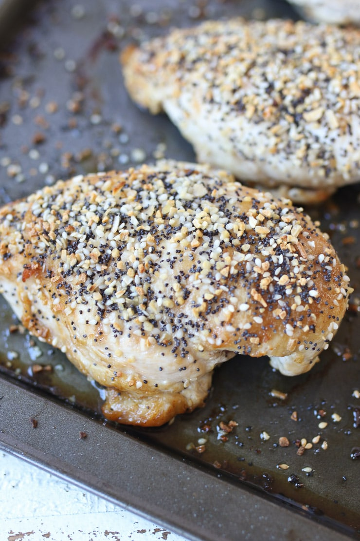 White meat topped with seasoning on a baking sheet.