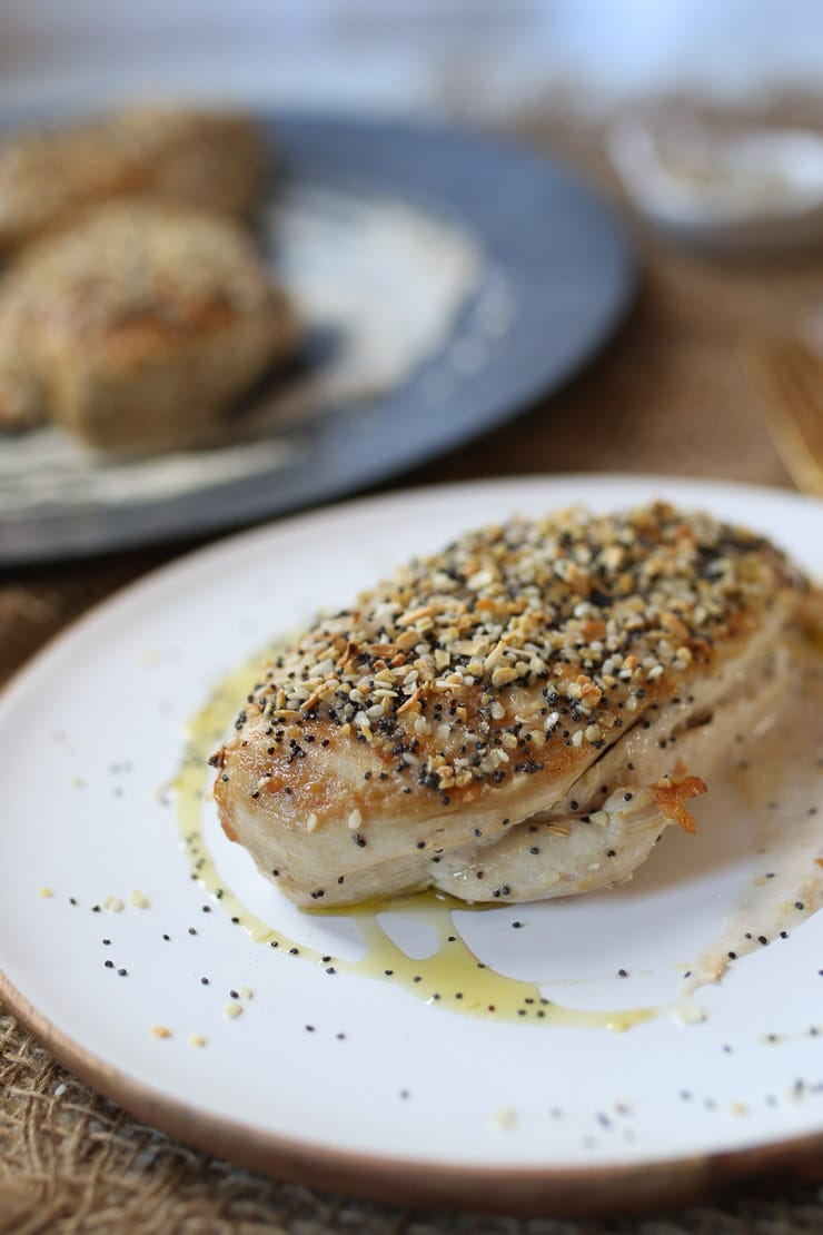 White meat everything bagel spiced chicken breast served on a white plate.