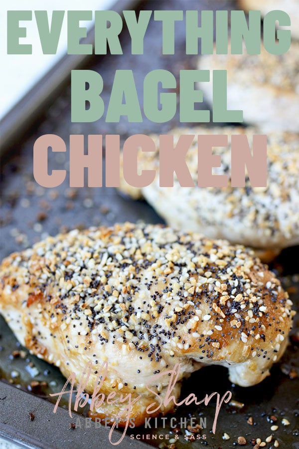 Chicken breasts topped with seasoning on a baking sheet.