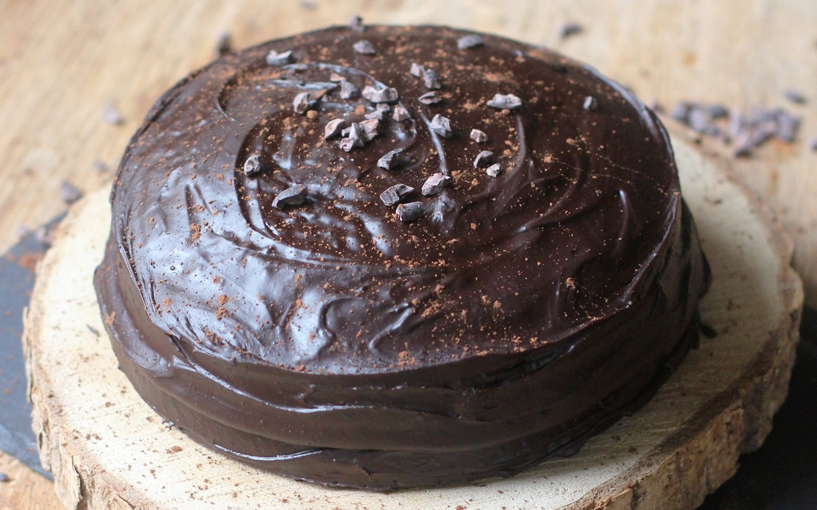 A close up of a piece of chocolate cake with chocolate frosting.