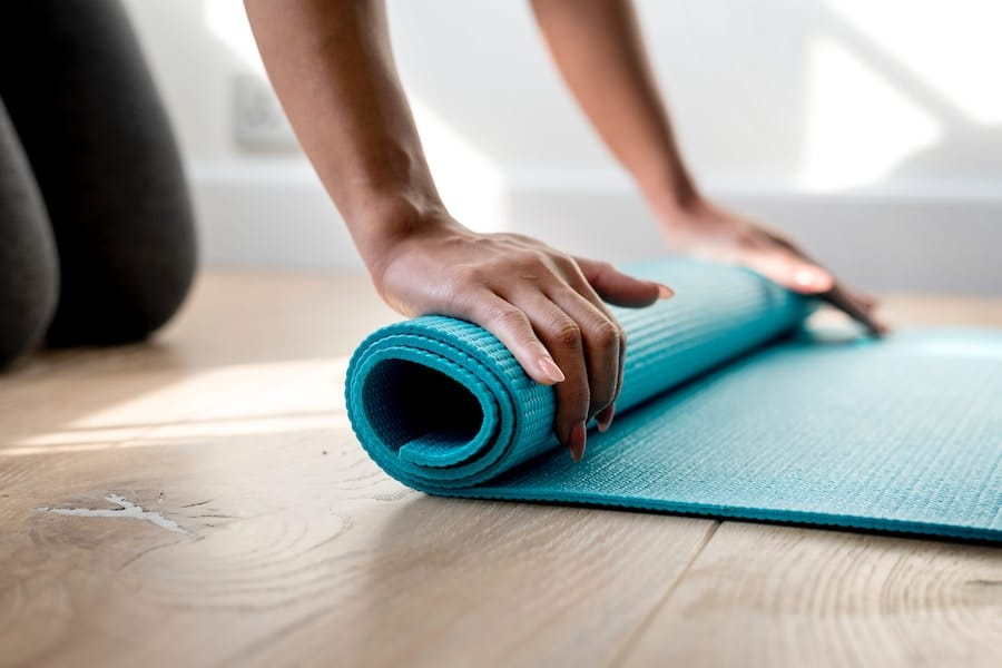 person rolling a yoga mat