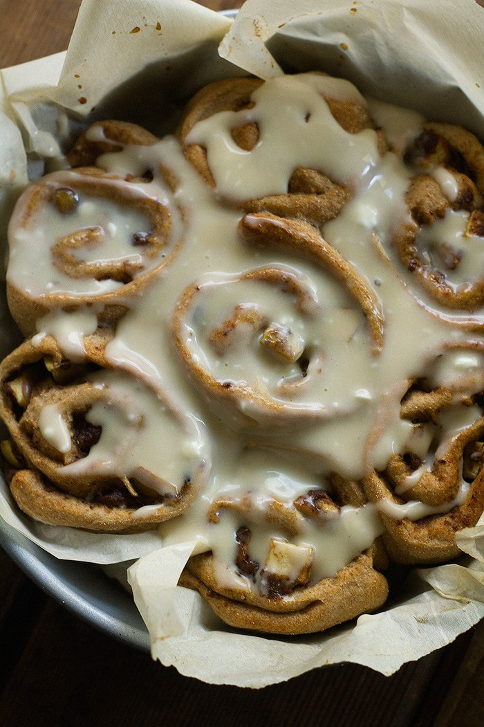 Cinnamon buns with icing in a baking tray.