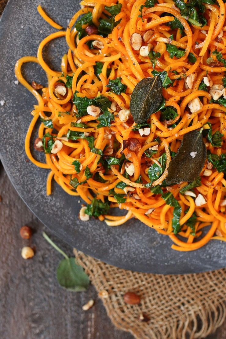 Close up of brown butter butternut squash zoodles topped with fried sage leaves and chopped hazelnuts.