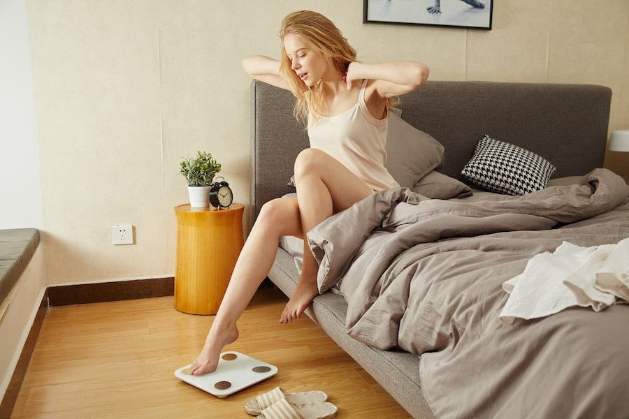 image of a woman sitting on her bed stretching