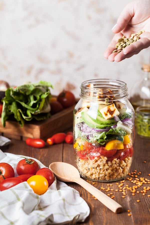 Mason jar layered salad being topped with seeds