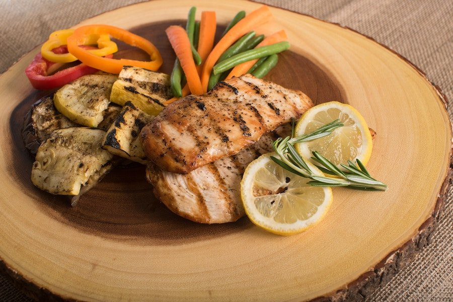grilled chicken and vegetables on a wooden plate