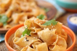 close up image of peanut butter noodles garnished with sesame seeds and cilantro in an orange bowl