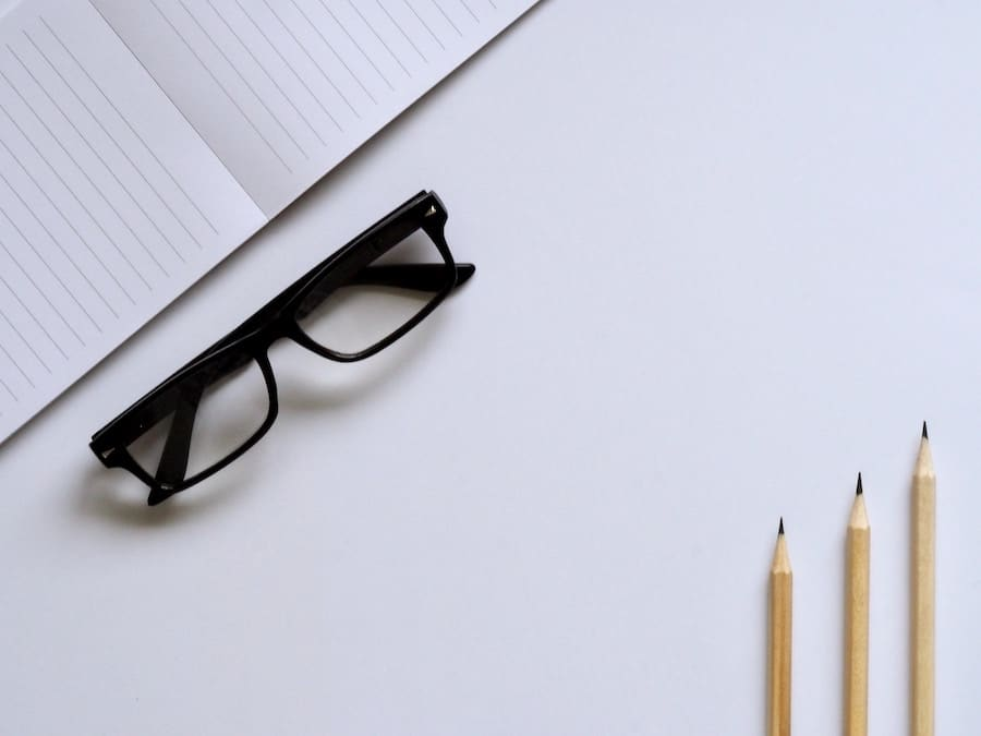 white desk with pencils, glasses, and a book