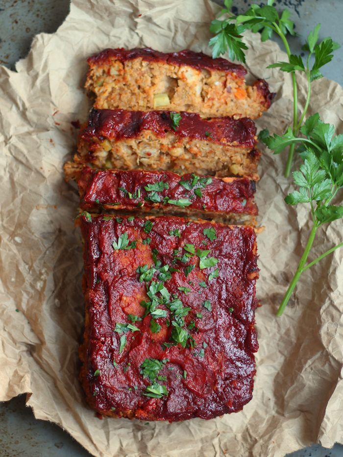 A birds eye view of a meat loaf with a few slices cut on brown paper and garnished with parsley.