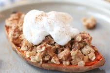 Close up of sweet potato stuffed with apple crisp topped with a vegan cream on a grey plate.