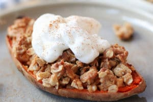 Close up of sweet potato stuffed with apple crisp topped with vegan cream on a grey plate.