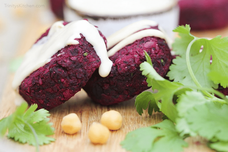 close up image of two roasted beetroot falafels garnished with herbs and tahini