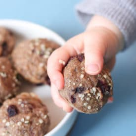 Baby hand holding mini muffin next to a white bowl filled with mini muffins.