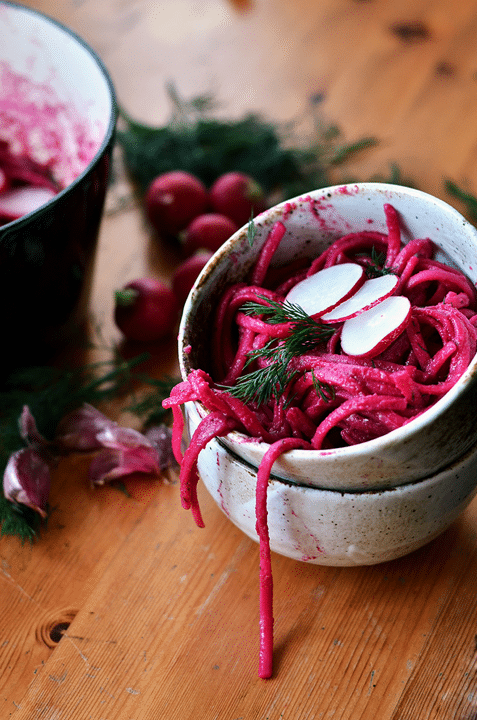 close up of vegan beetroot dill linguine in a small grey bowl garnished with radishes and herbs