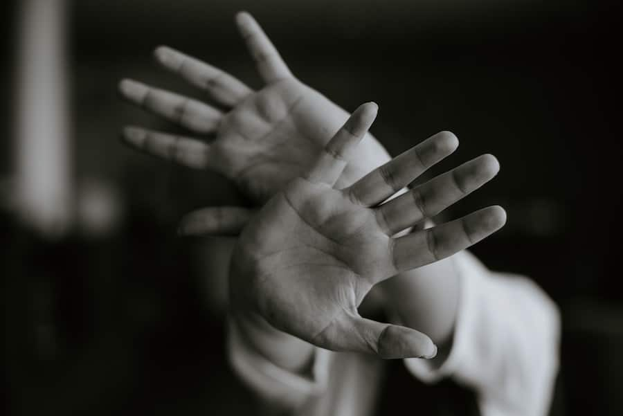 A close up of two hands waving in black and white.