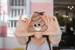 Person holding up a cookie shaped like a poop emoji.