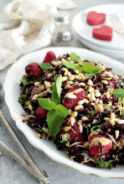 vegan black rice and raspberry salad garnished with pine nuts and fresh herbs in a large white dish