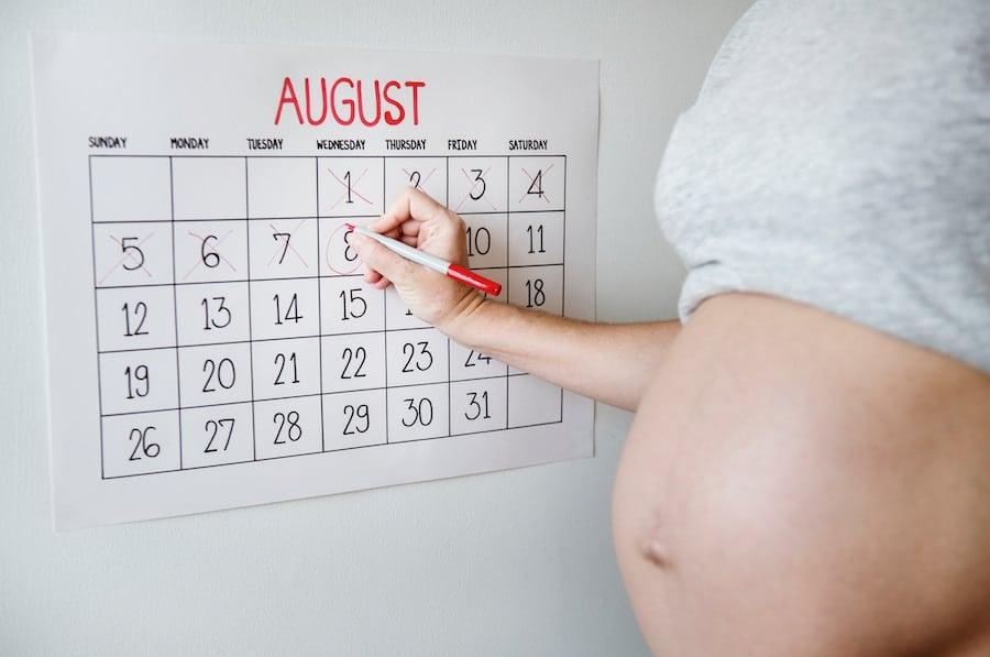 Pregnant women writing on a calendar.