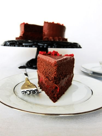 slice of vegan dark chocolate and red wine cake on a white plate