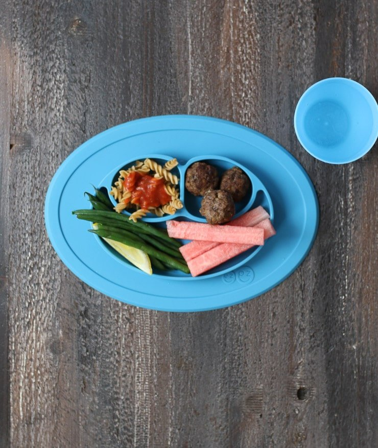Baby led weaning dinner on a blue plate containing pasta with tomato sauce, meatballs, green beans and watermelon.