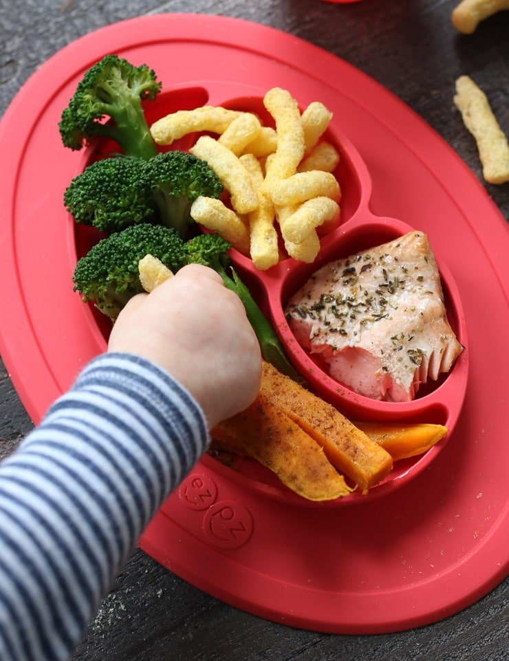 Baby grabbing at baby led weaning lunch on a red plate.