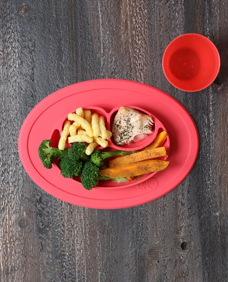 Baby led weaning lunch on a red plate containing broccoli, sweet potato, salmon and baby gourmet carrot sticks.
