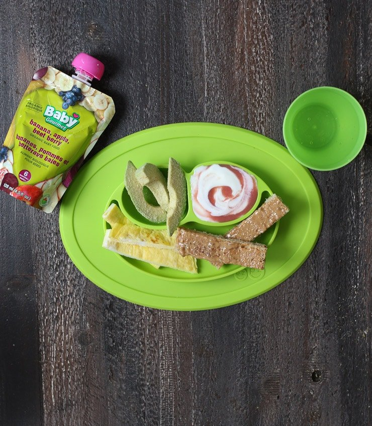 Baby led weaning breakfast containing strips of avocado, omelette, toast and yogurt.