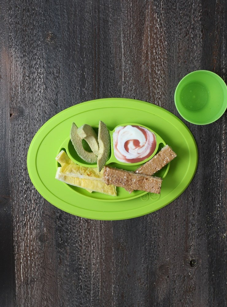 Baby led weaning breakfast containing slices of avocado, omelette strips, strips of toast and yogurt on a green plate